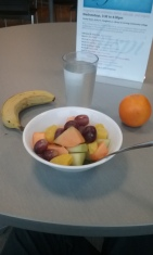 Bowl of fruit with fruit-infused water, banana, and an orange.